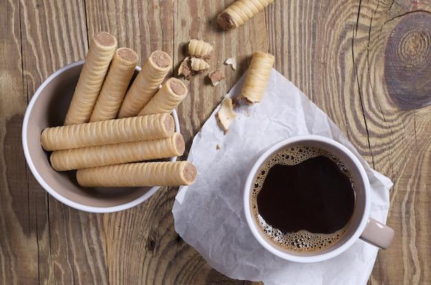 초콜릿 와플이 그릇에 담겨 있고 근처에서 부서지고 나무 탁자 위에 있는 커피 한 잔