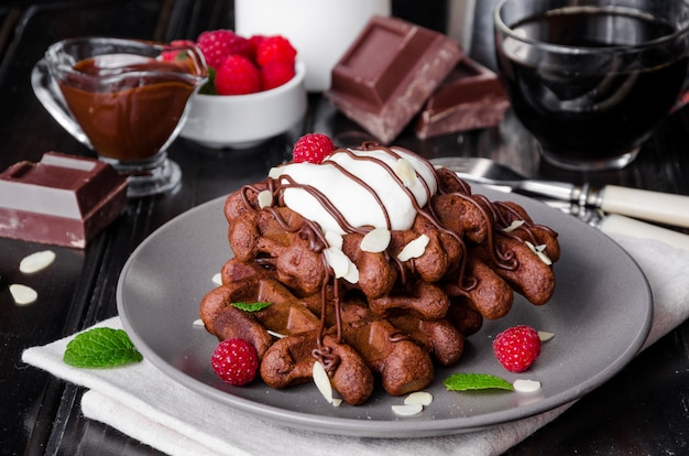 Chocolate waffles with glaze, whipped cream, almond petals and raspberries on dark wooden .