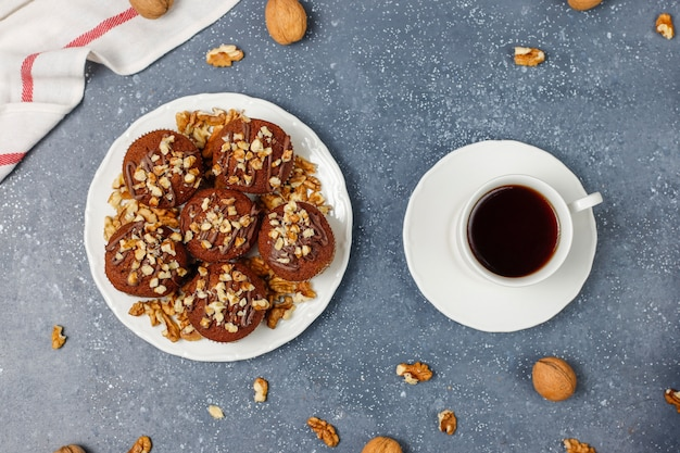 Chocolate-walnut muffins with coffee cup with walnuts on dark surface