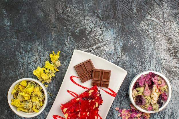 Cioccolato sul piatto bianco vicino a ciotole di fiori secchi su fondo grigio