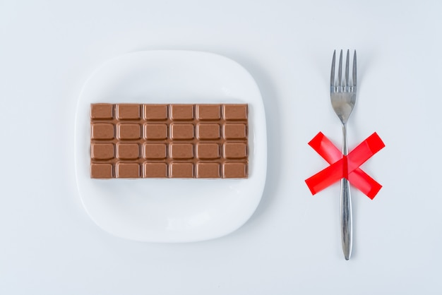 Chocolate on white plate with fork with red x cross on the table. dieting, unhealthy lifestyle concept