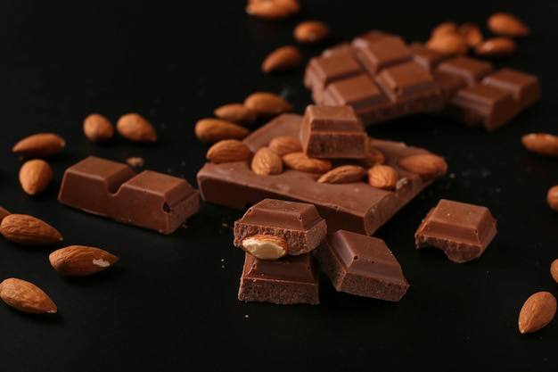 Chocolate with almonds and cinnamon on a dark surface