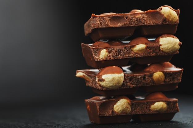 Chocolate with hazelnut on a black background close-up.