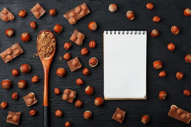 Шоколад с фундуком, блокнот с пустыми страницами и деревянная ложка с какао, окруженные орехами в скорлупе и очищенные.