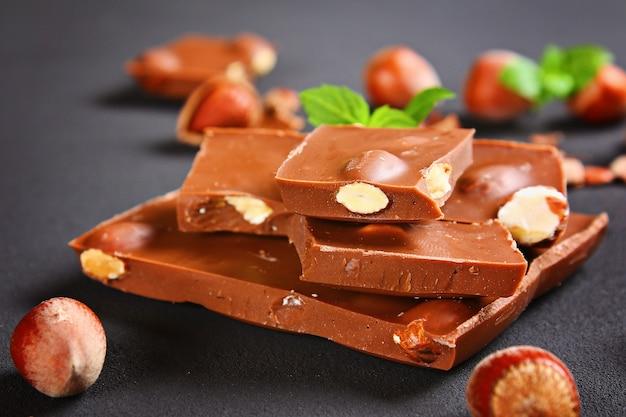 チョコレートには、ヘーゼルナッツ、ミント、コーヒーの穀物が濃いグレーのテーブルに置かれています。