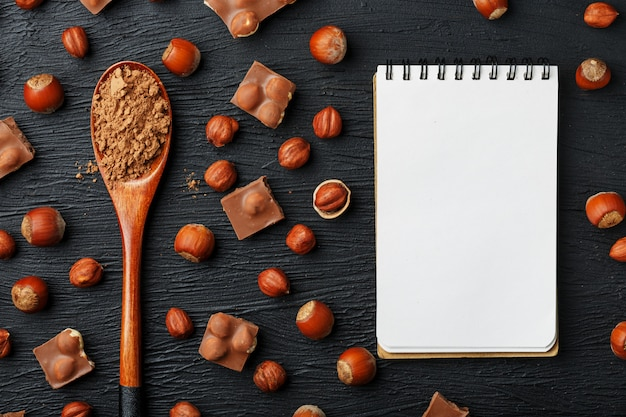 Chocolate with hazelnuts, a notebook with blank pages and a wooden spoon with cocoa on a dark background, surrounded by nuts in the shell and peeled.