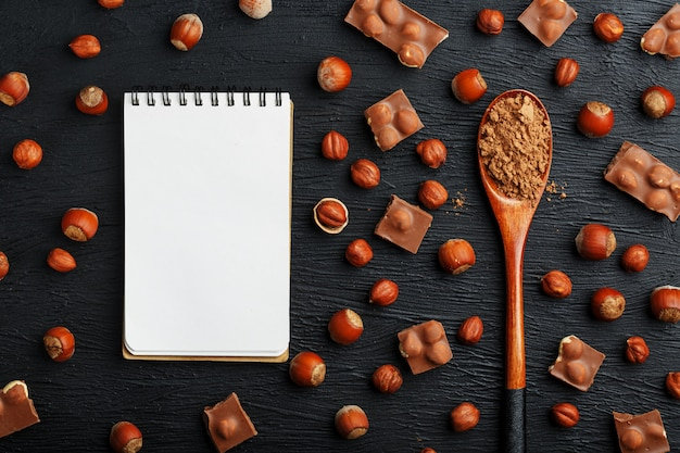 Chocolate with hazelnuts, a notebook with blank pages and a wooden spoon with cocoa, surrounded by nuts in the shell and peeled.