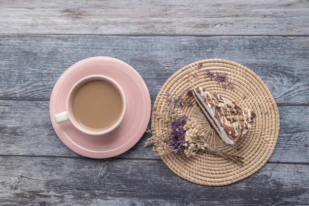チョコレートとマカダミア - アーモンドケーキケーキとホットコーヒー。木製のテーブルの背景