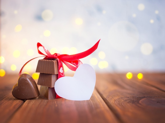 Chocolate with ribbon and heart on st. valentine's day and bokeh.