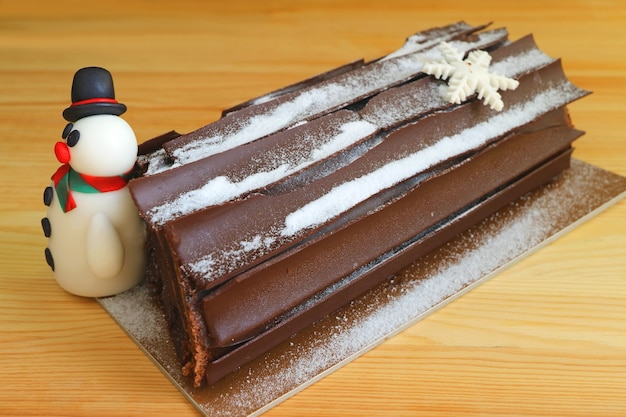 Chocolate yule log cake for with a cute snowman marzipan for christmas celebration