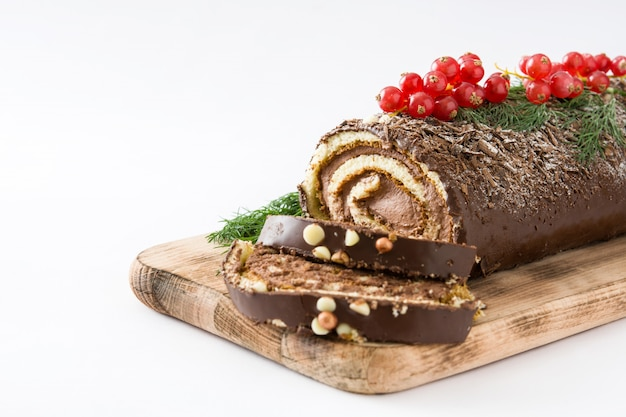 Chocolate yule log christmas cake with red currant isolated on white background.