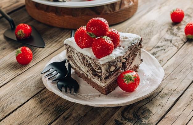 Шоколадный муссовый торт зебра с клубникой на деревянном деревенском фоне