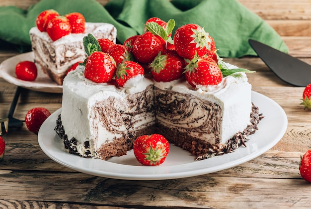 Chocolate zebra mousse cake with strawberry over wooden rustic background