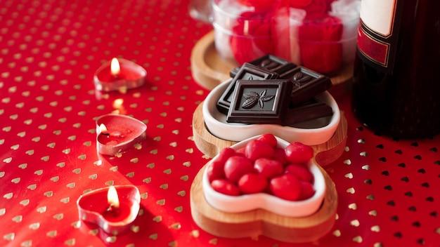 Конфеты и конфеты на тарелках в форме сердца. сервировка праздничного стола для свидания влюбленных. красный фон