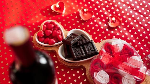 ハート型のプレートにチョコレートとお菓子。恋人たちのデートのためのお祝いのテーブルセッティング。赤い背景