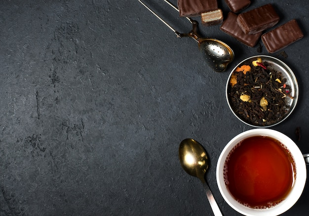 Chocolates and black tea with herbs. metal tea strainer, spoon.