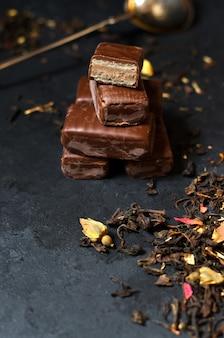 Chocolates and black tea with herbs. metal tea strainer.