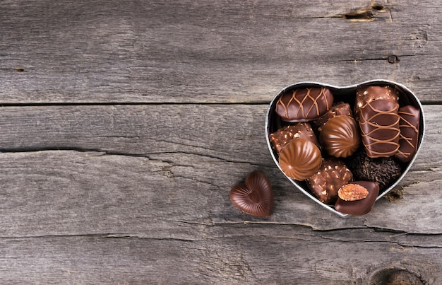 Chocolates in a box in form of heart on a dark background