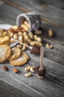 Cioccolatini, biscotti e noci sulla superficie in legno