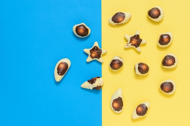 Chocolates in the form of sea shellfish and shells on a yellow and blue background.