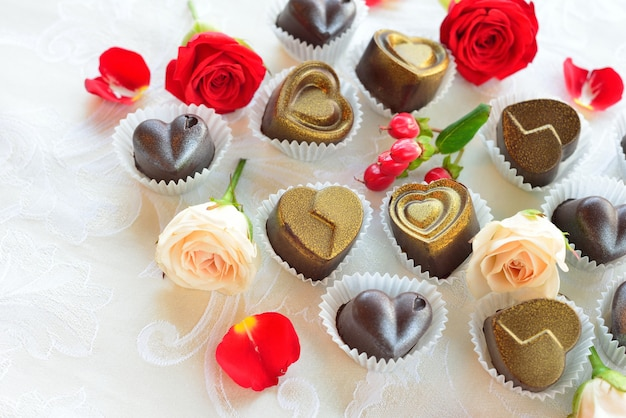 Chocolates in a heart shape made of milk and dark chocolate with the addition of gold and silver
