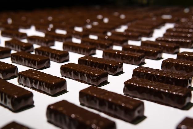 Шоколадные конфеты, только что залитые жидким шоколадом, на конвейерной ленте кондитерской фабрики.