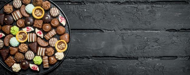 トレイにチョコレート。黒の素朴なテーブルの上。