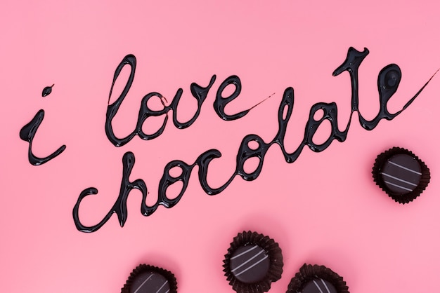 Chocolates on pink background with chocolate syrup writing