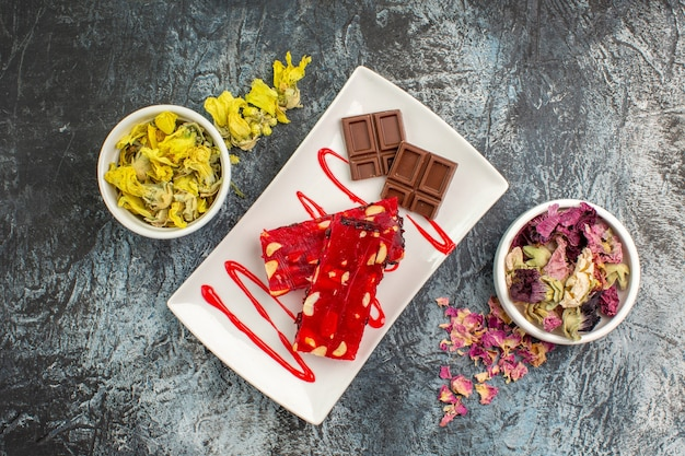 Cioccolatini sul piatto bianco vicino a ciotole di fiori secchi su fondo grigio