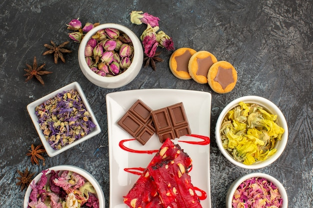 Cioccolatini sul piatto bianco con biscotti e strilli di fiori secchi su fondo grigio