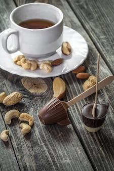 木製の背景にお茶とナッツとチョコレート