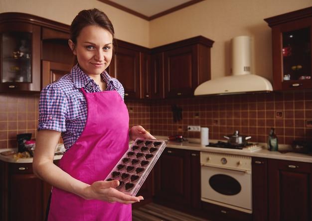 木製の家庭の台所の表面にチョコレートの殻でいっぱいの型でカメラにポーズをとるショコラティエ。世界チョコレートデーを祝うためのチョコレートの製造 Premium写真