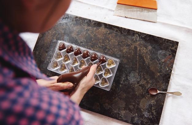 ショコラティエは、液体の温かいチョコレートの塊を菓子袋からキャンディーの型に絞ります。手作りの贅沢なチョコレートを作るプロセス。ハイアングルビュー。チョコレートの日の概念