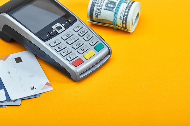 Choice among hundred dollar bills and credit cards on yellow background. concept of cash vs bank transfers.