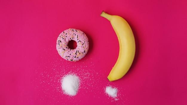 바나나에 대한 선택 도넛 - 음식의 설탕과 칼로리. 건강한 식사 또는 정크 푸드 시작. 분홍색 배경