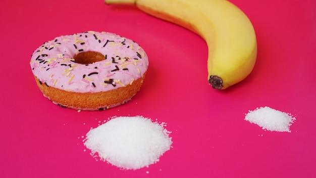 バナナに対するドーナツの選択-食品中の砂糖とカロリー。健康的な食事やジャンクフードを始める。ピンクの背景
