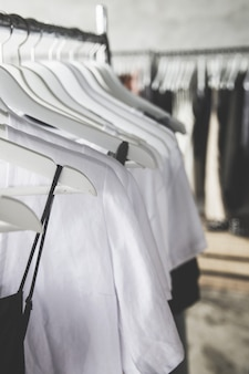 Choice of fashion clothes of different colors on wooden white hangers in a row