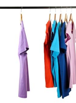 白で隔離の木製ハンガーにさまざまな色の服の選択