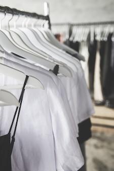 Выбор модной одежды разных цветов на деревянных белых вешалках подряд
