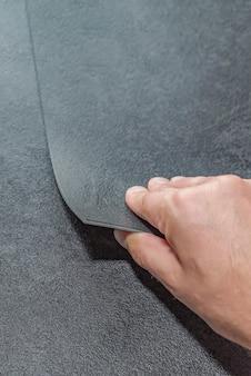 フローリングの選択。改修または建設の概念。テクスチャード加工のビニール床タイルを持っている男性の手のクローズアップ。ラミネートとビニールの床タイルのサンプル。
