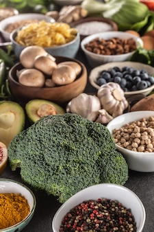 ブロッコリーを中心とした生鮮食品と健康的な食事の選択。コンクリートのテーブルに野菜、果物、豆類、シリアル。