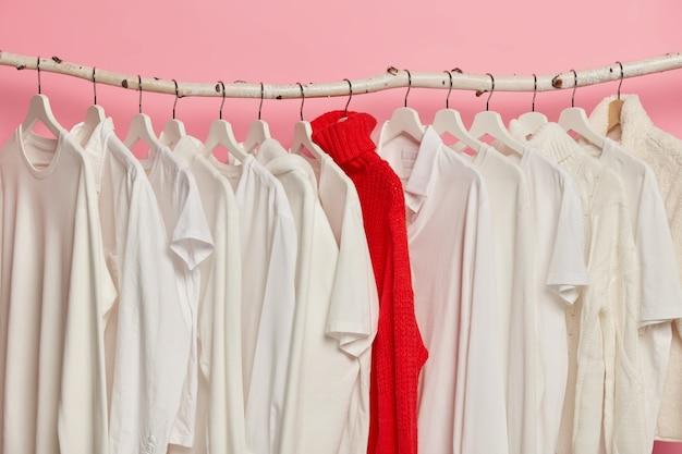 Выбор белой одежды на вешалках в магазине модной одежды. красный яркий вязаный свитер между нарядами в один тон, изолированный на розовой стене.