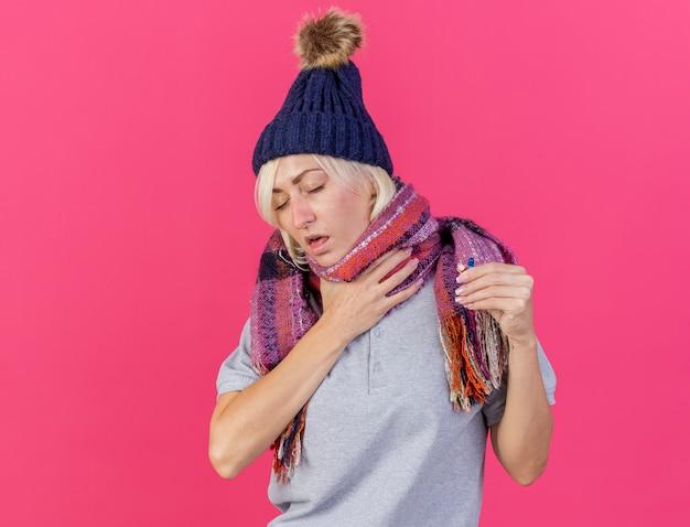 겨울 모자와 스카프를 착용하는 젊은 금발의 아픈 슬라브 여성이 목에 손을 댄다.