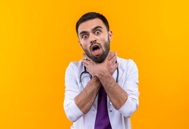 청진 기 의료 가운을 입고 질 식 젊은 남성 의사는 고립 된 노란색 벽에 목을 잡고
