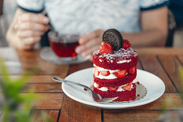 カフェで茶色の木製テーブルの上のイチゴとchokolateクッキーと赤いベルベットのケーキ