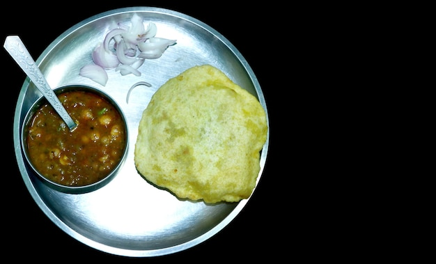 Chole bhature or chick pea curry and fried puri served in a plate and bowl over a black background with blank space for text