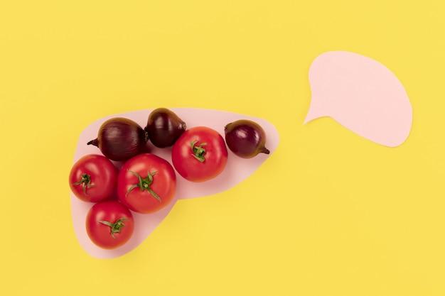 Холестериновая диета и здоровая пища, питательная для концепции сокращения сердечно-сосудистых заболеваний со свежими овощами в бумажной печени на желтом фоне. концептуальная композиция с copyspace