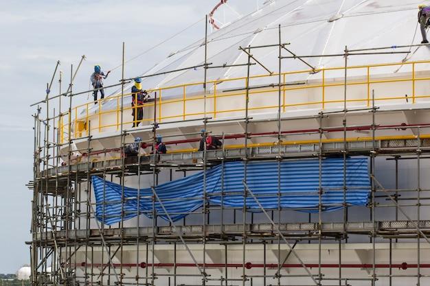 チョンブリタイ-2017年7月12日:足場貯蔵タンクを設置する建設作業員。