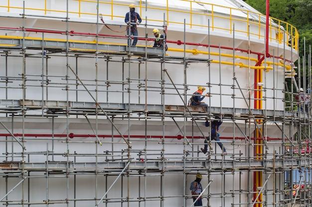 チョンブリタイ-2017年7月16日:足場貯蔵タンクを設置する建設作業員。
