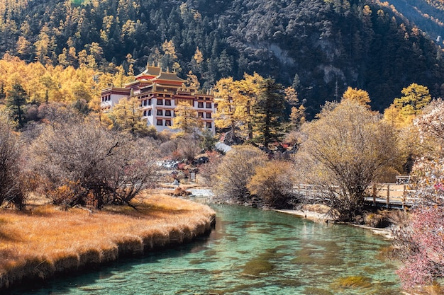 Chong gu temple on autumn hill with emerald river at yading